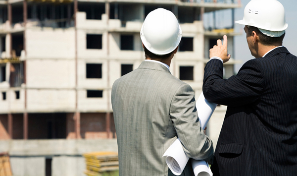 Two gentlemen wearing hard hats are looking at a building construction site